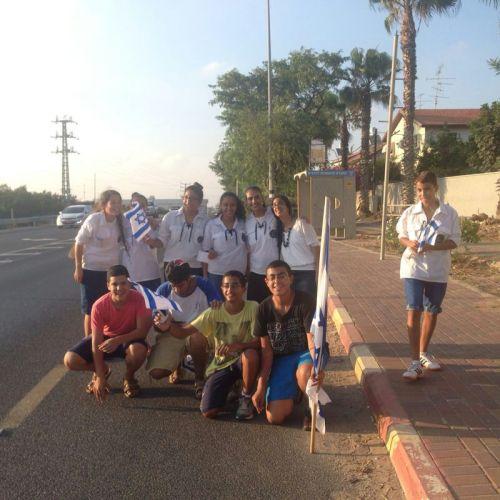בנות שירות עם חניכים מהיישוב עם דגלי ישראל