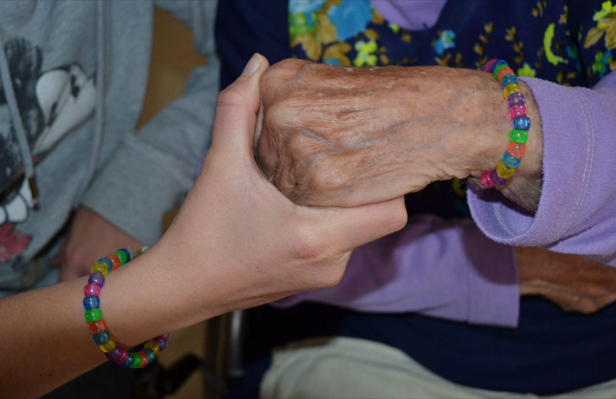 בת שירות וקשישה מוהדרת מחזיקות ידיים