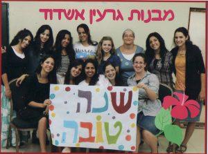 """בנות גרעין אשדוד בתמונה קבוצתית מחזיקות שלט שכתוב עליו """"שנה טובה"""""""