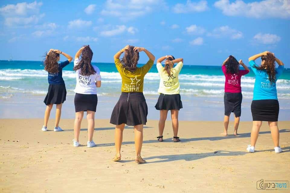 בנות השירות של נותנים תקווה בים עם חולצות של נותנים תקווה