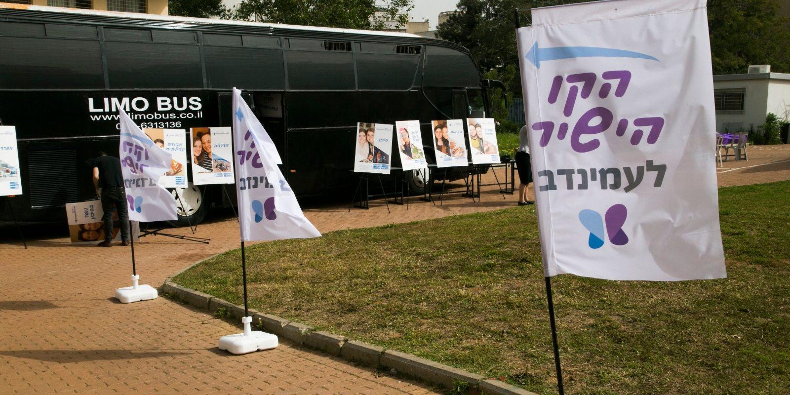 אוטובוס עמינדב ולידו שלטים עם תחומי השירות